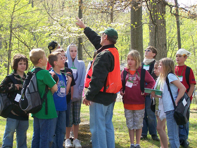 A volunteer with a group of children standing around him shares his favorite facts about trees.