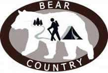 Bear Country in oval around white bear with silhouetted hiker, tent and trail to trees