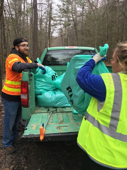 Two smiling volunteers pile bags of trash into the bed of a forest service pickup.