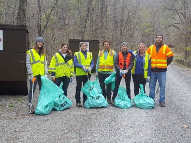 A group of seven volunteers stand proudly in yellow caution vests, smiling in front of bags of trash