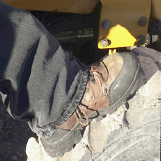 Photo of a person's leg wearing black pants and hiking boot with their foot resting on a tire.