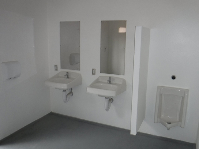 Photo shows a urinal and two sinks, each spotless and new.