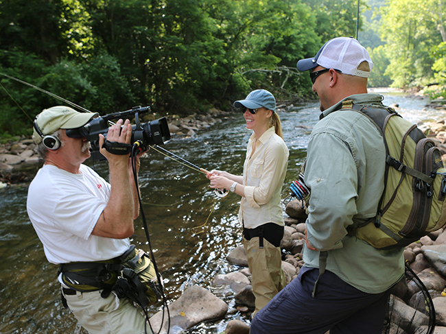 Darly Newman and representatives from trout unlimited stand in front of a camera.