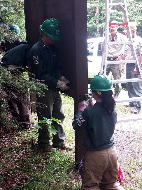 Members of Vermont YCC install signage at a trailhead.