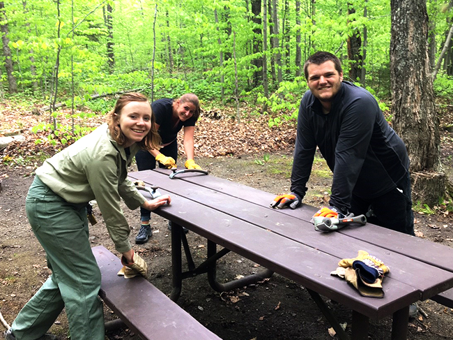 Forest Service staff build a picnic table at a campsite.