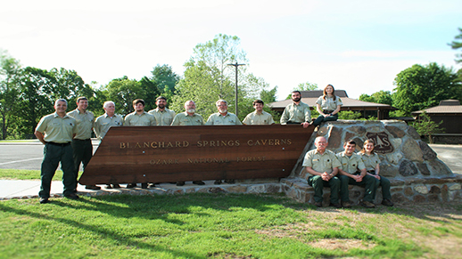 The employees at Blanchard Springs Caverns are pictured around the entrance sign