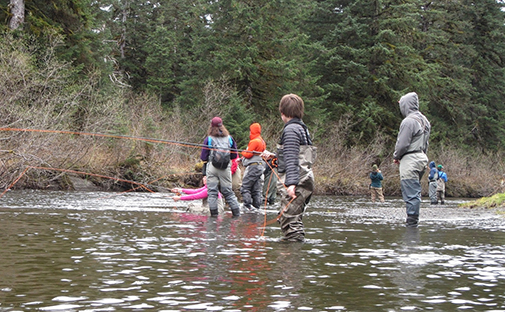 Yakutat School youth stand in the Situk River with fly fishing poles