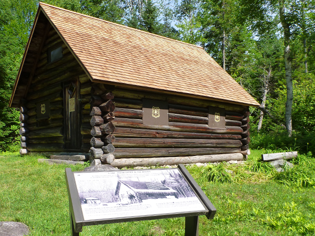 An interpretive panels sits in the foreground of a photo of the Fabyan Guard Station today.