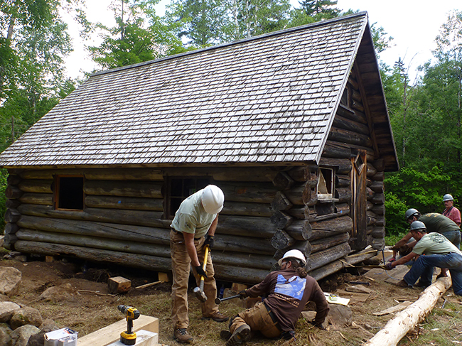 A team of volunteers work to restore the small cabin .