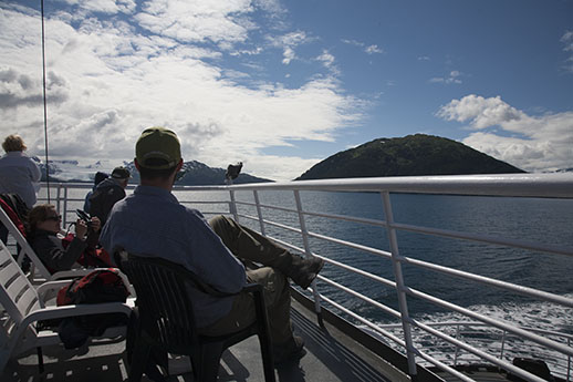 A group of people on the ferry looking at the scenery.