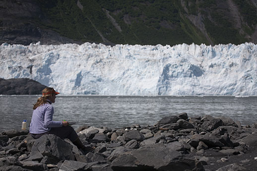 A woman sitting on the shore with water between her and a wall of glacial ice.