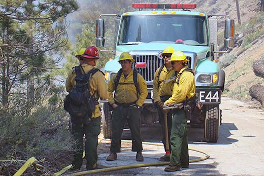 Four individuals wearing hard hat and fire gear stand together in front of a vehicle.