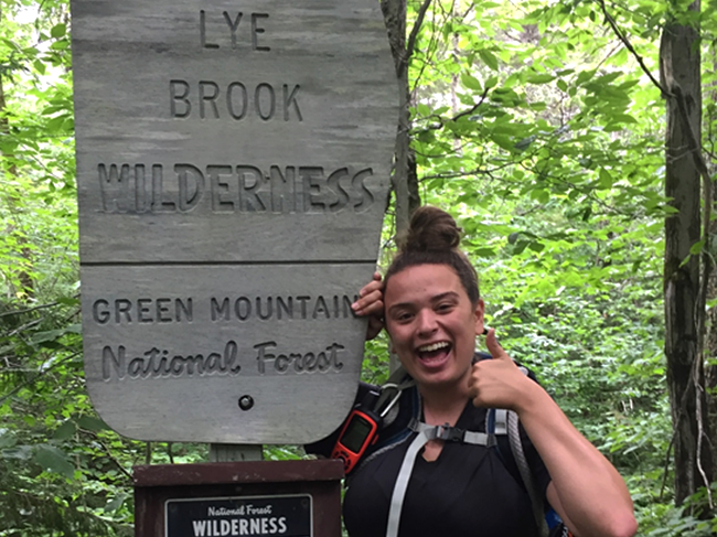 A young woman poses with the sign for the Lye Brook Wilderness area Green Mountain National Forest