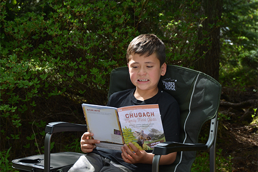 Little boy in a chair reading the family field guide.