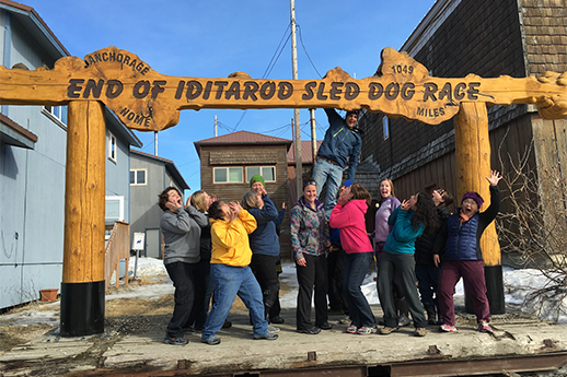 "Particpants in Nome, Alaska standing in front of the ""End of the Iditarod Sled dog race"" sign."