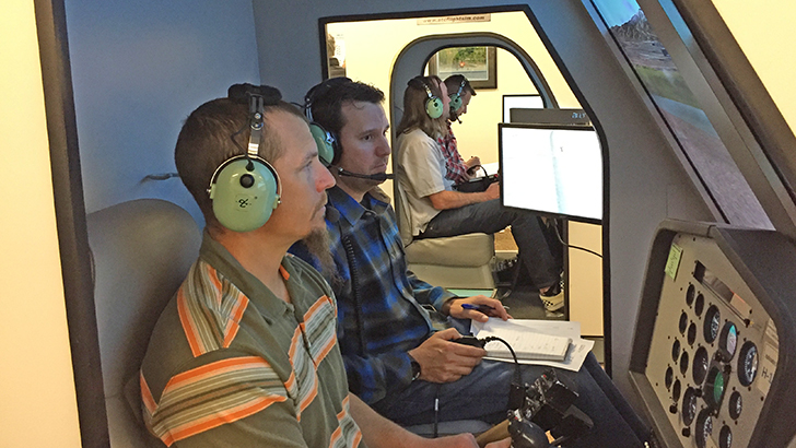 Men and women sit inside helicopter simulation cockpits.