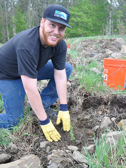 A kneeling map smiles for the camera as he plants a tree into the tilled soil.