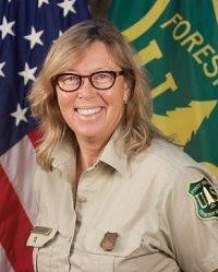 A woman in Forest Service Uniform smiles into the camera.