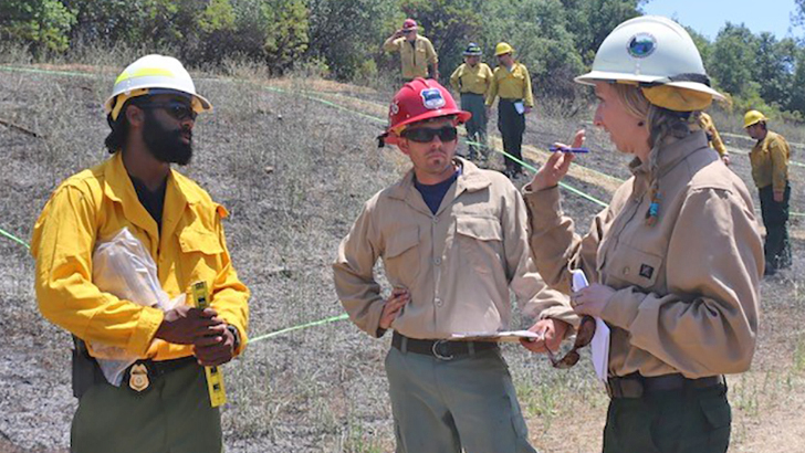 A female firefighter talks to students while standing in a field.