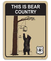 A bear reaches for a well hung bear bag. Text reads This is Bear Country.