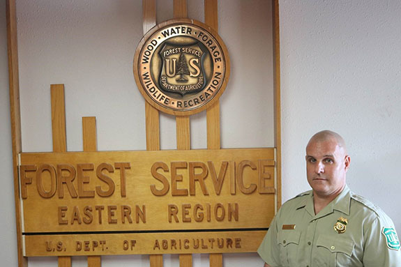 Paul Joyner standing next to Forest Service Eastern Region Sign