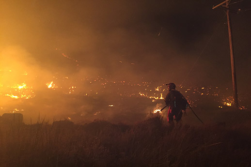 A firefighter standing with a torch overlooking an evening fire scene.
