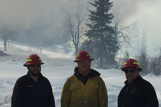 Three firefighters standing in front of a pile-burn in winter.