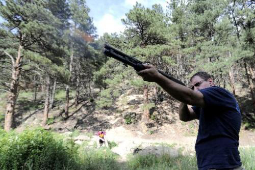 A man target shooting in the forest