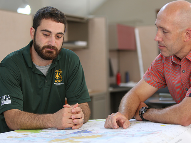 Two men discuss the USDA Forest Service Resource Assistants (RA) Program