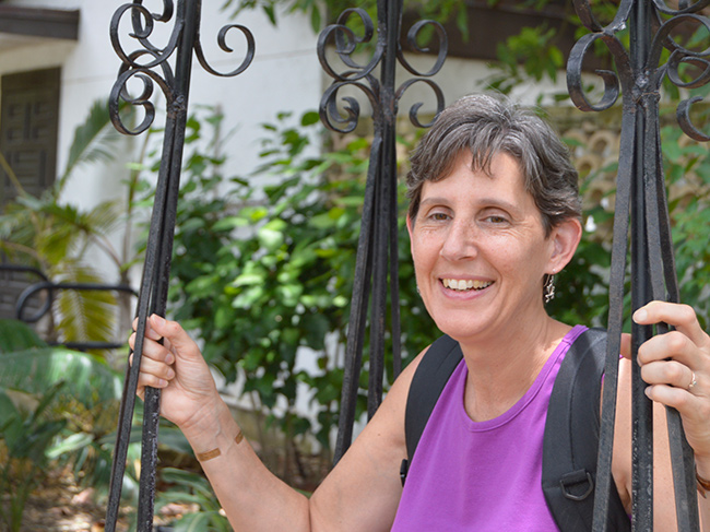 Marion Mason poses along a wrought iron fence while traveling.