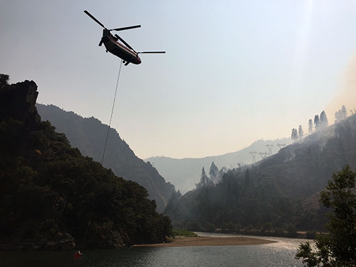 Helicopter with bucket dropped into river getting water with smoke filled mountains in background