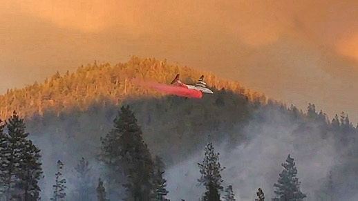An airplane releases red substance in the air while flying over smokey landscape.