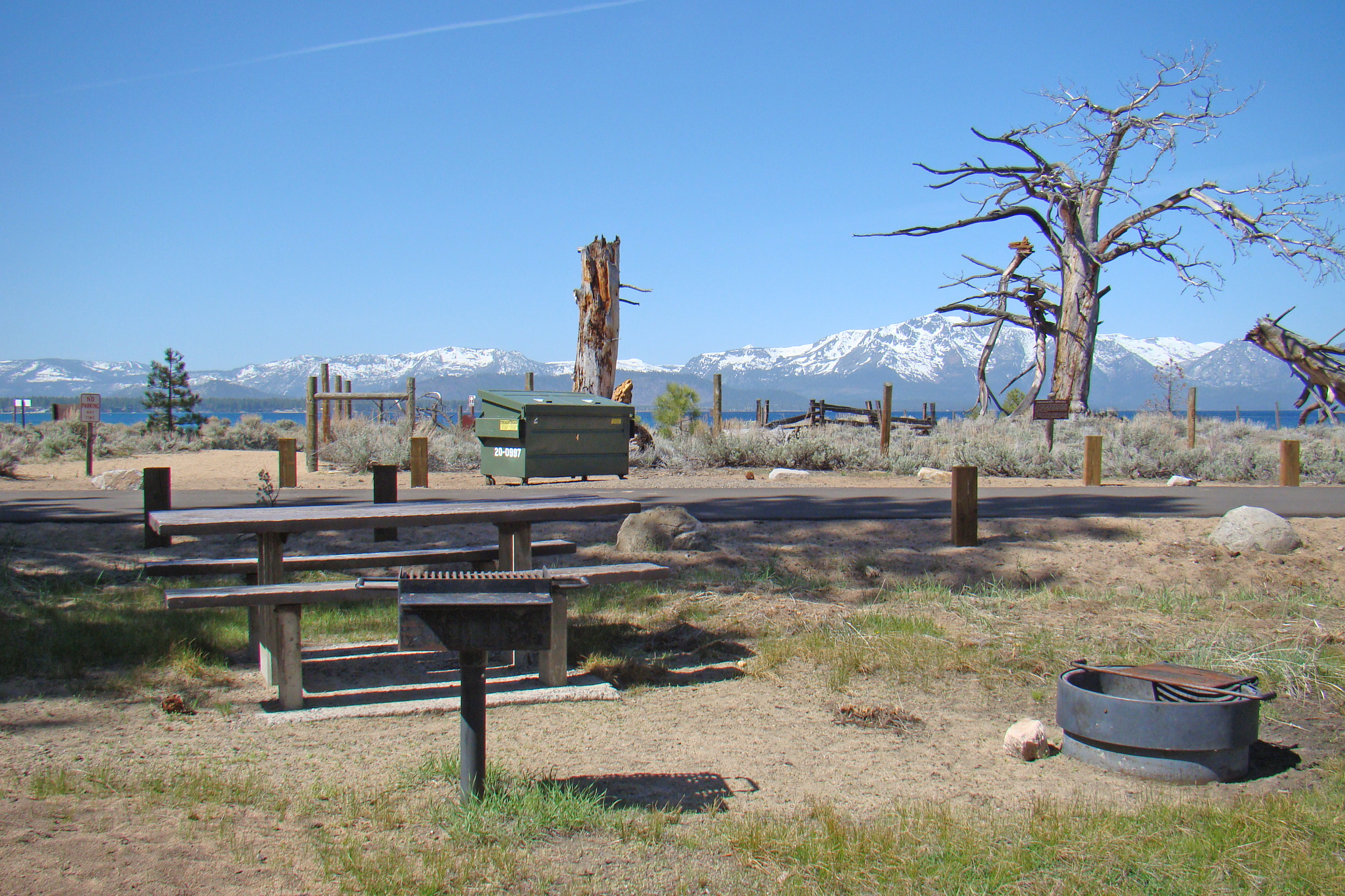 Picnic table, campfire ring and stand up grill at Nevada Beach with Lake Tahoe in the background.