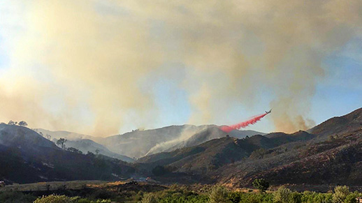 Amid smoky skies, an airplane drops red retardant on hillsides