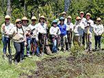 Teenagers learn about forest management, how to saw logs, plants trees, clear trash, maintain trails