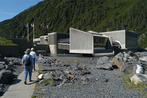 Two people walking the lake trail in front of the Begich, Boggs Visitor Center.