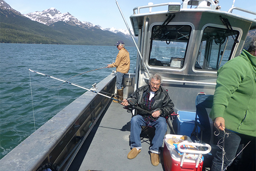 An older gentleman sitting down and fishing from the side of a large boat