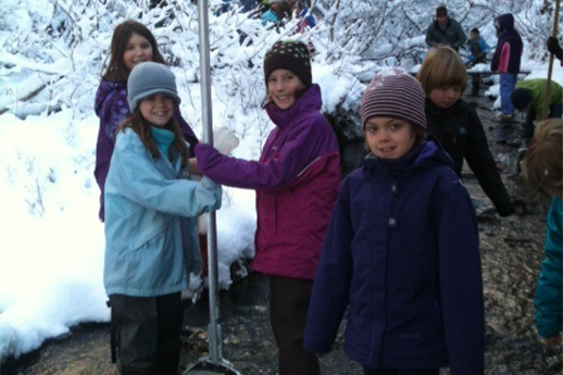 A group of school-age children working on an outdoor project in along a snowy river bank.
