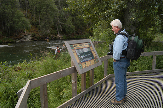 A man standing on a boardwalk reading an interpretive sign.