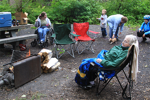 A variety of people in a campground – an older woman, woman in a wheelchair, a young child, woman with a dog and a bicyclist