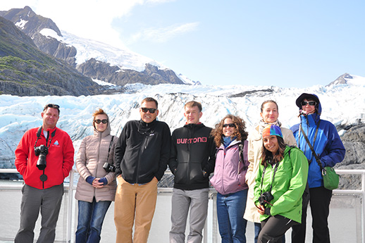 A group of international visitors in front of a glacier.