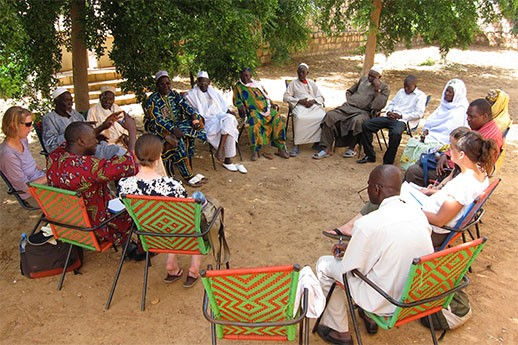 A circle of people discussing natural resource issues in Mali, Africa