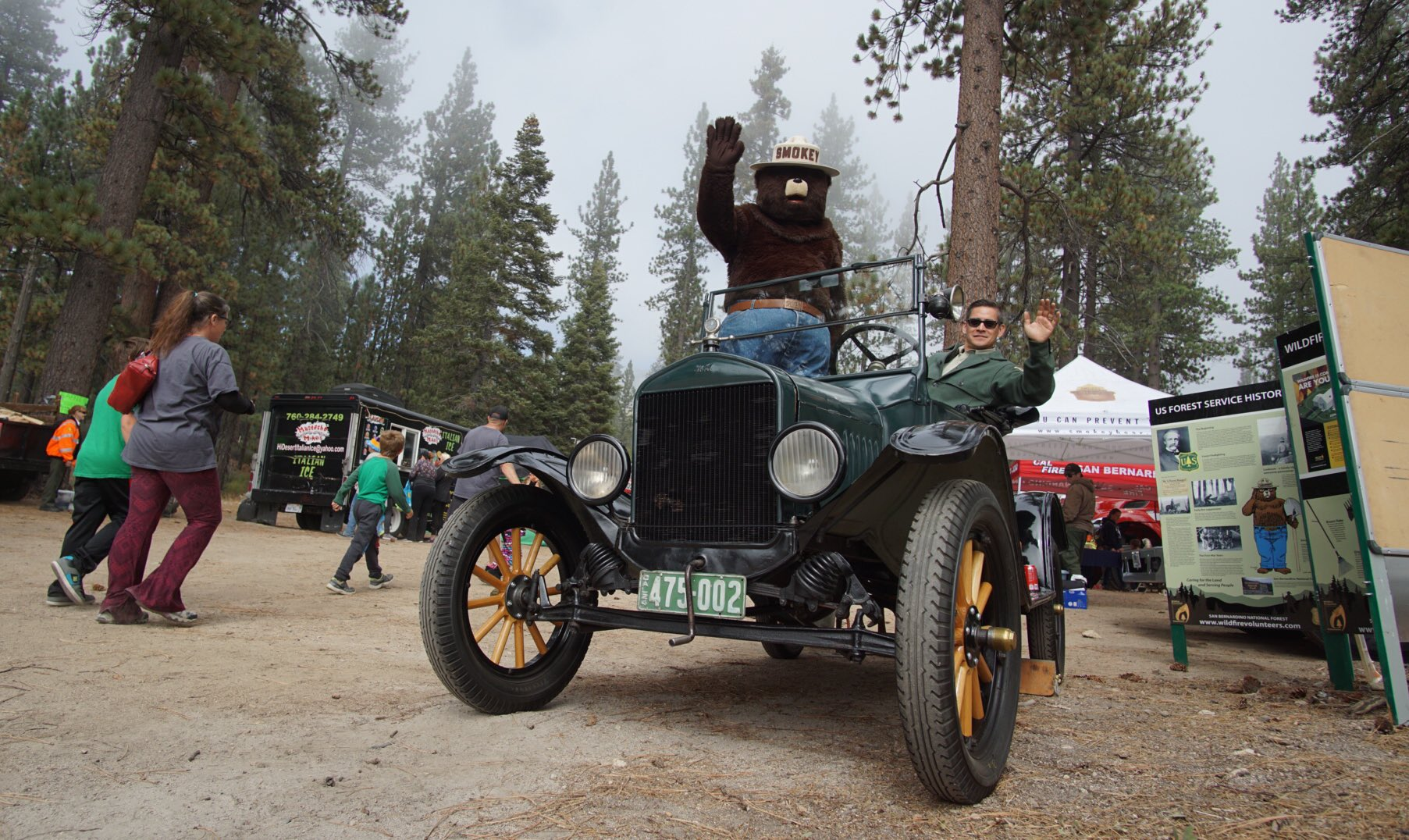 Smokey Bear and a Forest Service employee wave from a black 1924 Model T fire vehicle.