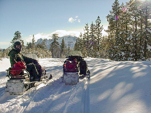 Two snowmobiles, one with a man on the seat,  in the snow in the mountains