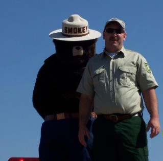 A man and Smokey Bear posing for a photo.
