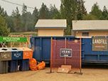 Recycling bins, netting and a dumpster sit ready for customers at a fire incident command area.