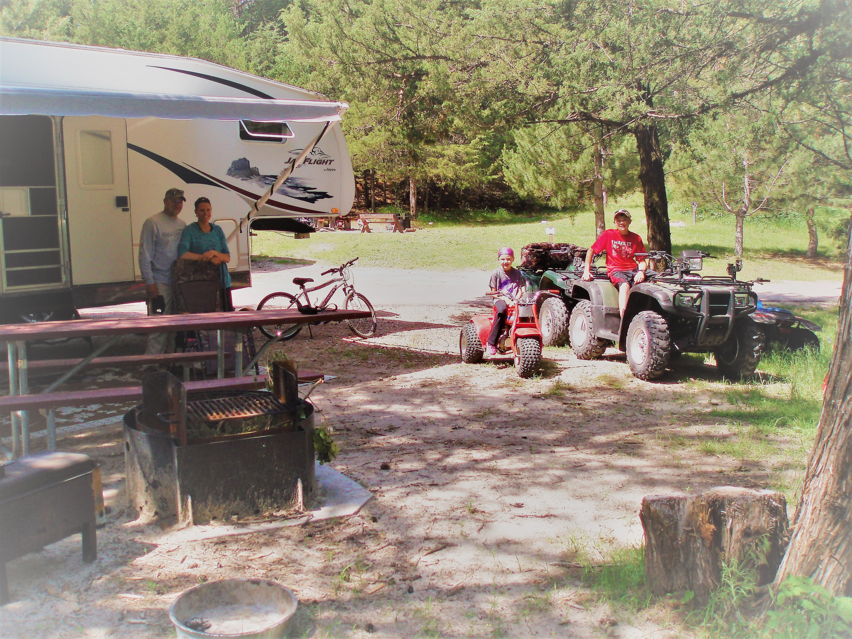 A family in front of their RV at one of the campsites.