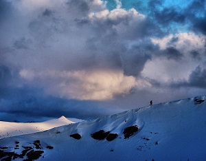 A solo skier against a purple sky with snow at Vale Pass