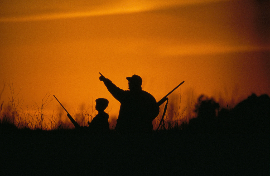 Sunset hunter and child sihouette