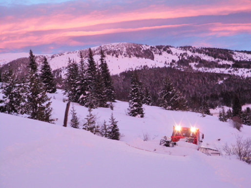 The sun rises on the slopes as a grooming machine smooths the slopes.